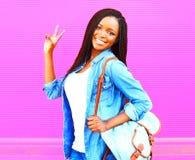 Mujer africana joven feliz con la mochila sobre rosa Imagen de archivo libre de regalías