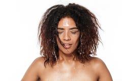 Mujer africana joven feliz limpia su cara con agua Imagen de archivo