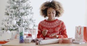 Mujer africana joven feliz que envuelve presentes almacen de video