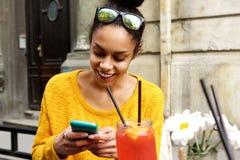 Mujer africana joven feliz que se sienta en el café Foto de archivo libre de regalías