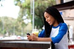 Mujer africana joven feliz que se sienta en el café al aire libre usando el teléfono móvil fotografía de archivo