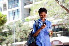 Mujer africana joven fresca que camina al aire libre en ciudad usando el teléfono móvil Foto de archivo libre de regalías