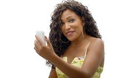 Mujer africana joven hermosa con el teléfono celular fotografía de archivo libre de regalías