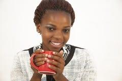 Mujer africana joven hermosa que sostiene una taza de café Imagenes de archivo