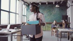 Mujer africana joven que consigue encendida de trabajo La hembra camina a través de la oficina, llevando la caja con los objetos