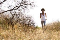 Mujer africana joven que corre en rastro de montaña Imagen de archivo libre de regalías