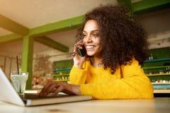 Mujer africana joven que disfruta de su tiempo libre en un café Fotografía de archivo libre de regalías