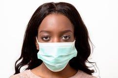 Mujer africana joven que lleva una mascarilla quirúrgica Imagen de archivo libre de regalías