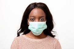 Mujer africana joven que lleva una mascarilla quirúrgica Imagenes de archivo