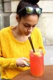 Mujer africana joven que se sienta en un café al aire libre Fotografía de archivo libre de regalías