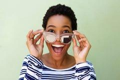 Mujer africana joven que sonríe con las gafas de sol contra la pared verde Foto de archivo libre de regalías