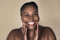 Mujer africana joven que sonríe y que toca su tez perfecta foto de archivo libre de regalías