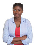 Mujer africana joven sonriente con los brazos cruzados Imagenes de archivo
