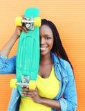 Mujer africana joven sonriente feliz con el monopatín sobre colorido Fotos de archivo