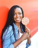 Mujer africana joven sonriente feliz con la piruleta dulce Imagen de archivo