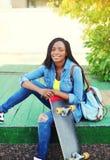 Mujer africana joven sonriente hermosa con el monopatín Foto de archivo libre de regalías