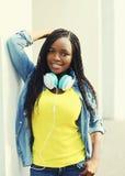Mujer africana joven sonriente hermosa con los auriculares Fotografía de archivo