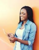 Mujer africana joven sonriente hermosa que usa la PC de la tableta Fotografía de archivo