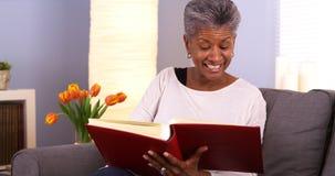 Mujer africana madura feliz que mira a través de álbum de foto foto de archivo