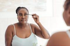 Mujer africana que aplica el rimel en un espejo del cuarto de baño en casa imagen de archivo libre de regalías
