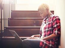 Mujer africana que busca Internet que se sienta en pasos foto de archivo