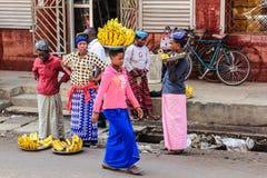 Mujer africana que camina con un manojo de plátanos en su cabeza Imagen de archivo