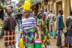 Mujer africana que camina con un tanque amarillo en la cabeza Fotos de archivo libres de regalías