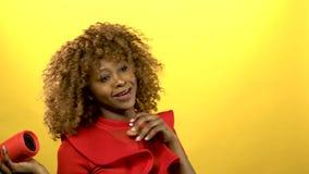 Mujer africana que celebra un jugador y un baile Fondo amarillo almacen de video