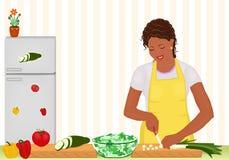 Mujer africana que cocina la ensalada en la cocina Foto de archivo