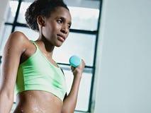 Mujer africana que ejercita con los pequeños pesos en gimnasia Fotografía de archivo