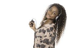 Mujer africana que escucha la música del teléfono Imagen de archivo libre de regalías