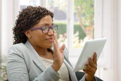 Mujer africana que habla en línea con la tableta fotografía de archivo libre de regalías