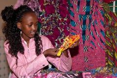 Mujer africana que muestra gotas y telas amarillas Foto de archivo libre de regalías