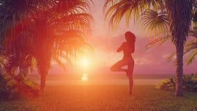 Mujer africana que reflexiona sobre la playa en actitud del árbol de la yoga