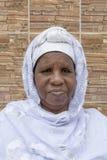 Mujer africana que se sienta delante de su casa, sesenta y cinco años fotos de archivo libres de regalías