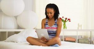 Mujer africana que se sienta en cama usando la tableta Fotos de archivo libres de regalías