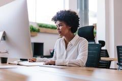 Mujer africana que trabaja en su escritorio de oficina imagen de archivo libre de regalías