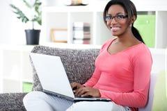Mujer africana que usa el ordenador portátil Fotografía de archivo libre de regalías