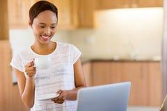 Mujer africana que usa la computadora portátil Imágenes de archivo libres de regalías