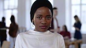 Mujer africana seria joven del director empresarial en el turbante étnico que mira la cámara, sonriendo en la oficina de moda del metrajes