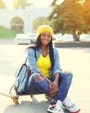 Mujer africana sonriente bastante fresca con el monopatín Fotografía de archivo