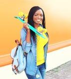 Mujer africana sonriente de los jóvenes hermosos con el monopatín Foto de archivo libre de regalías