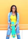 Mujer africana sonriente de los jóvenes hermosos con el monopatín en ropa colorida Fotografía de archivo libre de regalías
