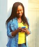 Mujer africana sonriente feliz de la moda que usa smartphone Imagen de archivo