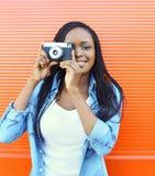 Mujer africana sonriente feliz del retrato con la cámara vieja del vintage Foto de archivo