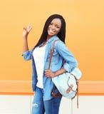 Mujer africana sonriente feliz hermosa del retrato con la mochila Imagenes de archivo