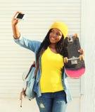 Mujer africana sonriente hermosa con el monopatín que toma la imagen del autorretrato en smartphone fotos de archivo