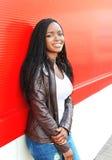 Mujer africana sonriente hermosa del retrato que lleva una chaqueta de cuero en ciudad Imagen de archivo