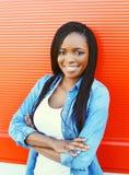 Mujer africana sonriente hermosa del retrato sobre rojo Imagen de archivo libre de regalías
