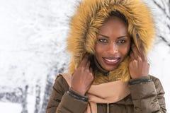 Mujer africana sonriente hermosa que lleva un abrigo de pieles y una capilla sobre nieve en día de invierno Fotografía de archivo libre de regalías